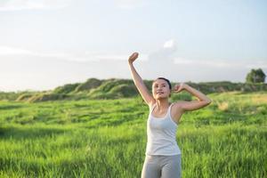ung vacker kvinna lyfter armarna i den friska luften i gröna ängar foto