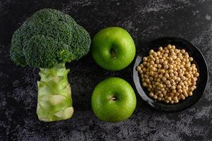 broccoli, äpple och bönor på en svart cementgolvbakgrund foto