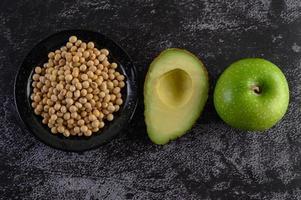 avokado, äpple och sojabönor på svart cementbakgrund