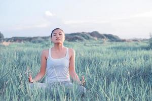 yogakvinna i lotusställning i en solig äng foto