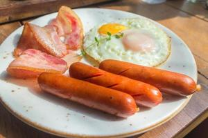 bacon, stekte ägg och korv på den vita plattan och träbord
