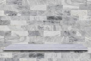 vit marmorhylla med stenbakgrund foto
