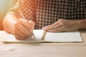 person som skriver i en dagbok foto