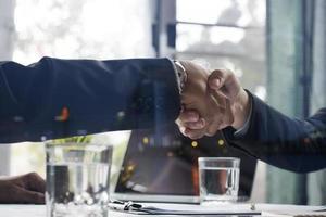 två affärsmän som skakar hand över en affär foto