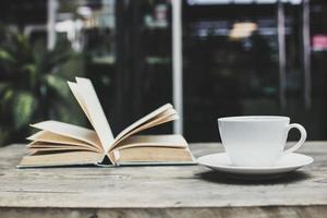 kaffemugg och en öppen bok foto