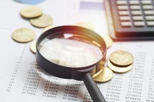 förstoringsglas på ett skrivbord med papper och mynt foto