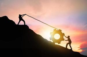 två personer rullar ett redskap uppför en klippa