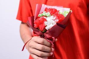 person som håller en blommig bukett foto