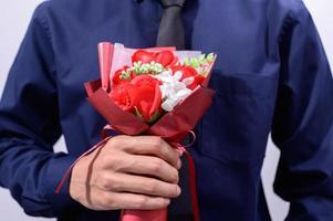 man som håller blommor foto