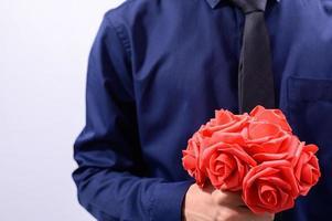 man som håller röda blommor foto