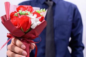 man som håller ut blommor foto