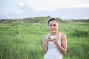 vacker asiatisk kvinna som dricker kaffe på en äng foto
