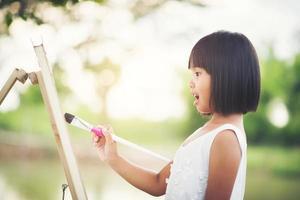 liten flickakonstnär som målar en bild i parken foto
