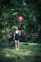 ung flicka som håller färgglada ballonger i naturen