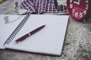 anteckningsbok med penna och väckarklocka, i vintage toneffekt foto