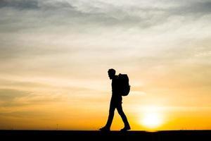 silhuett av en ung backpackersman som går under solnedgången