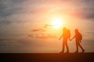 silhuetter av två vandrare med ryggsäckar som njuter av solnedgången