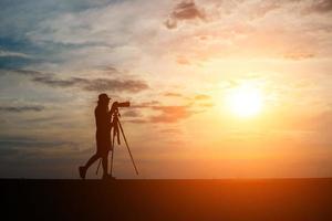 silhuett av en fotograf som skjuter vid solnedgången foto