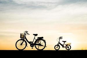 två vintage siluettcyklar vid solnedgången foto