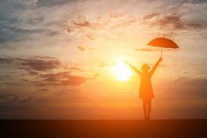 silhuett av en kvinna som håller ett paraply på stranden och solnedgången foto