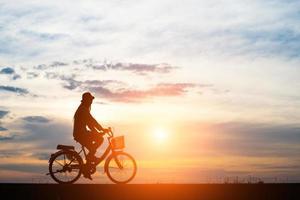 ung man cyklar på solnedgången bakgrund