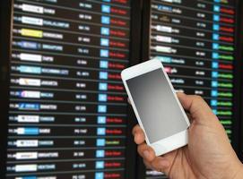 hand som håller telefonen nära flyginformation foto