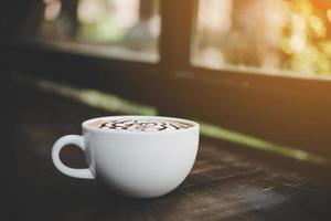 en kopp kaffe på ett träbord