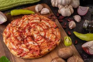 pizza på en träskiva med paprika, vitlök, chili och shiitakesvamp