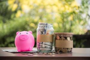 pengar i en glasburk i naturen, investeringskoncept foto