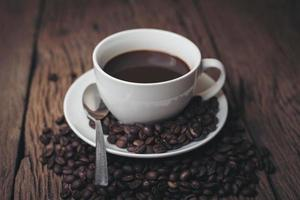 kaffekopp med kaffebönor på ett träbord