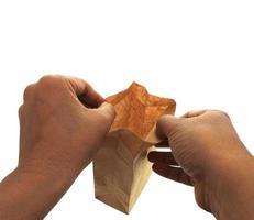 person som öppnar papperspåse