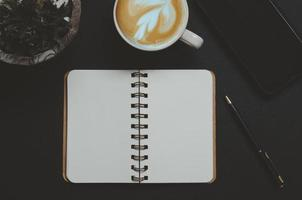 ovanifrån av en öppen anteckningsbok och en latte foto