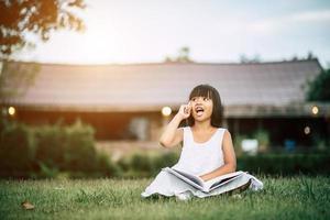 liten flicka som läser en bok i hennes husträdgård utanför foto