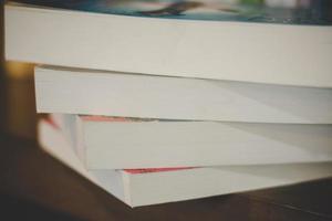 närbild av en hög med böcker på ett träbord foto