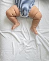 barnets fötter i en vit säng