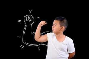 ung pojke visar sin muskelstyrka foto