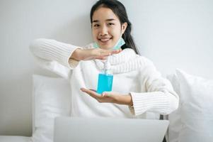 ung kvinna på sängen som rymmer handtvättgel foto