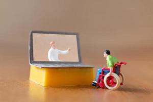 manlig statyett patient konsulterar med läkare med hjälp av videosamtal på bärbar dator foto