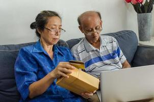 två äldre människor handlar online foto