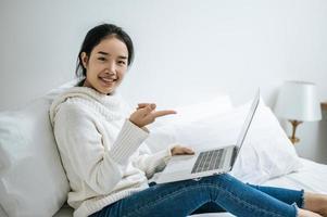 ung kvinna som bär en vit skjorta som spelar på sin bärbara dator foto