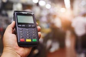 person som håller kreditmaskin foto