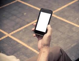 håller smart telefon med vit skärm foto