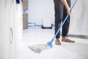 person som moppar golvet foto