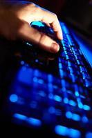 person som skriver på ett blått tangentbord foto