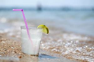 glas saft på stranden foto