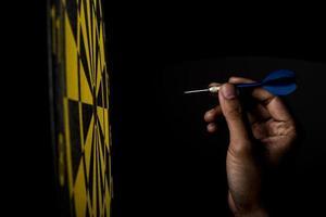 darttavla med pilen på svart bakgrund, framgångskoncept foto
