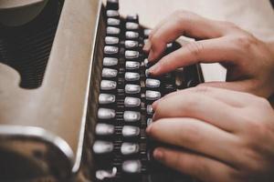 händer att skriva på vintage skrivmaskin på träbord