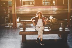 ung hipster turist kvinna med ryggsäck sitter i tågstationen