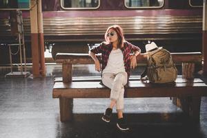ung hipster turist kvinna med ryggsäck sitter i tågstationen foto