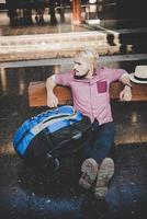 ung hipster man sitter på träbänk på järnvägsstationen